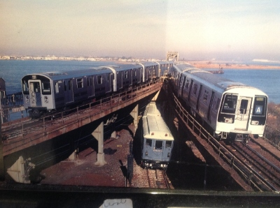 [New York]This MTA postcard shows the evolution of three types of trains on the New York Subway. Amazingly the picture was taken on the A Subway line to JFK Airport and Far Rockaway. The views are more akin to the Florida Keys than a subway system. A ride beyond the airport certainly beats waiting too long in the departure lounge and costs nothing if you do not leave the statin at the far end and just return to Howard Beach for the Skytrain to JFK