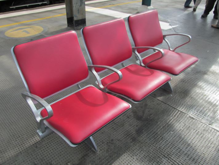 Most stations in Britain have hard seats (as do some trains and trams). Sometimes there are comfortable seats in waiting rooms. At Carlisle station there are padded seats on the platform itself. This is extremely rare. However, Carlisle does benefit from a station roof that covers all of the platforms and tracks