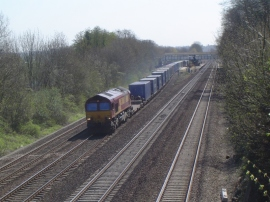 Locomotive in EWS colours hauls a train load of containers