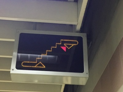 Escalators are spread along Metro platforms but singly to reduce the width of the station box and hence minimise construction costs. These moving signs are clearly visible directing passengers where to go for the escalator, which varies.