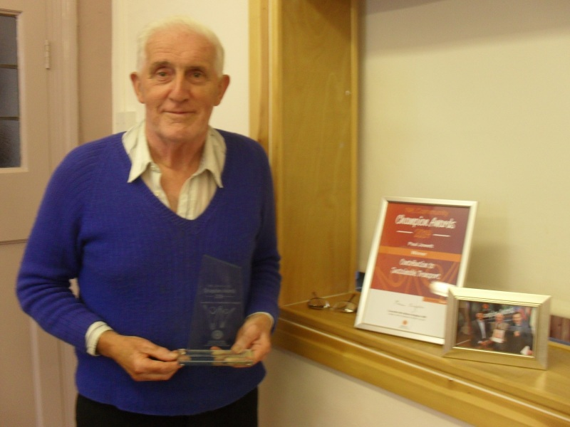 Long-term Railfuture member and volunteers, Paul Jowett, who died in 2019, standing beside a Community Champion 2014 award that he was given